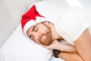 man med santa hatt som sover i sängen foto