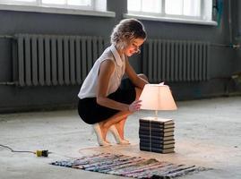 kvinna med böcker och ljusa glödlampor foto