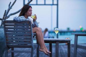 ung flicka med vitt vin på kvällens utomhuscafé foto