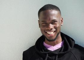 närbild porträtt av en glad ung svart man leende foto