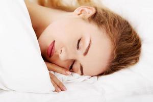 sovande kvinna som ligger i sängen foto