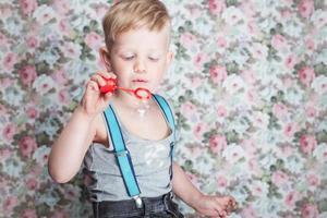 porträtt av rolig liten pojke som blåser såpbubblor