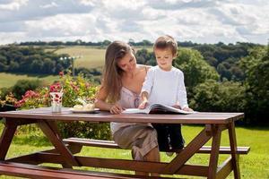 mamma och son och läser en bok utomhus, sommardag foto