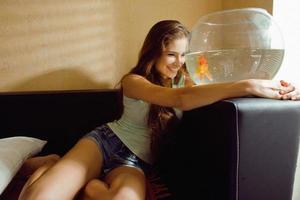 vacker kvinna som leker med guldfisk hemma, solljus morgon foto