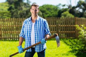 ung man med en hacka i trädgården foto