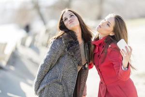 glada unga kvinnor som tar foto med mobiltelefonen