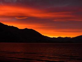 vatten och berg under orange molnig himmel foto