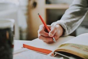närbild av person som skriver i bok