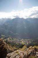 solstrålar som lyser ner på berg och stad foto