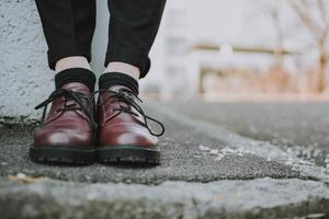 närbild av person som bär läderskor foto