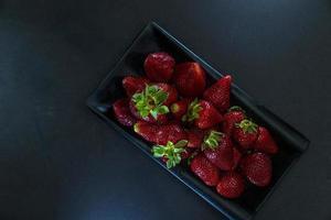 jordgubbar i svart behållare foto