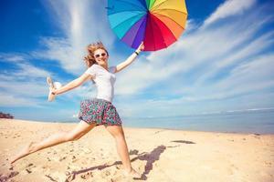 glad ung flicka med regnbågens paraply som har kul på foto