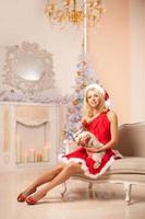 ung vacker leende santa kvinna nära julgranen med foto
