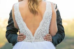 brudgummen håller brudens midja foto