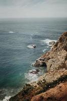 brun klippa nära havet foto