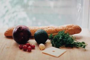 grönsaker bredvid bröd foto