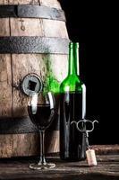 glas vin och flaska i den gamla källaren foto