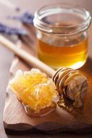 honungskakadippare och glasburk på träbakgrund foto