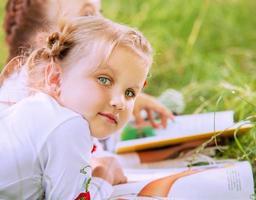 närbild porträtt söt liten flicka som läser en bok foto