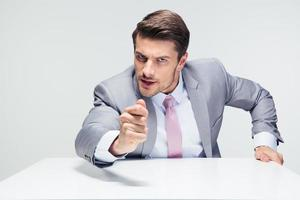 arg affärsman som sitter vid bordet foto