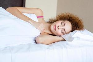 vacker kvinna med lockigt rött hår som sover i sängen foto