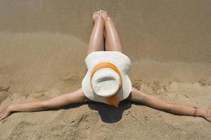 flicka med stråhatt som sitter på sandstranden foto