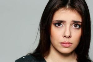 närbild porträtt av en ung sorglig kvinna foto