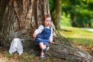 liten söt flicka som har kul i parken, sommar foto