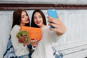 två flickor gör selfie med gåva foto