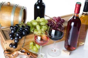 sammansättning med glasögon, flaskor vin och druvor foto