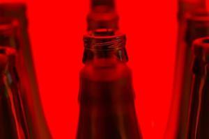 tio gröna flaskor i tre rader sköt med rött ljus. foto