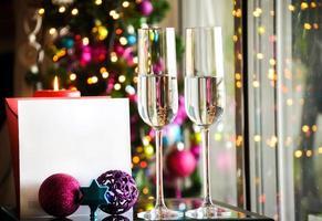 två champagnerglas på glasbord med bokehbakgrund foto