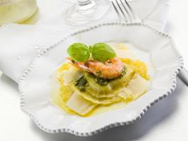 pesto ravioli med räkor och parmesanflingor foto