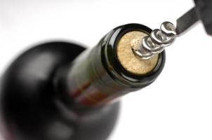 korkskruv och flaska vin foto