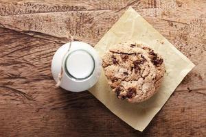 färsk mjölk och kakor på träbakgrund foto