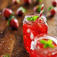 gammaldags burkar med livlig röd jordgubbecocktail foto