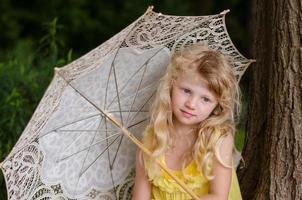 liten flicka som håller parasoll foto