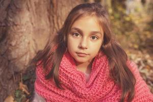 bedårande liten flicka utomhus i skogen foto