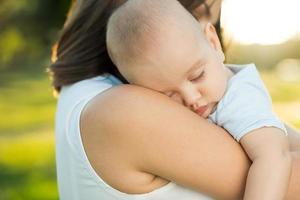 lycklig mamma som rymmer en ung sovande son foto