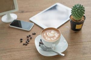 kopp kaffe på bordet i café med surfplattan foto