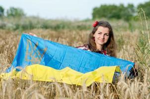 flicka i ukrainska nationella kostym, flagga poserar på vete fält