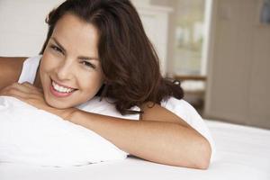 avslappnad kvinna i sängen leende foto