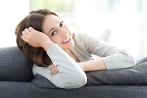 kvinna avkopplande på soffan foto