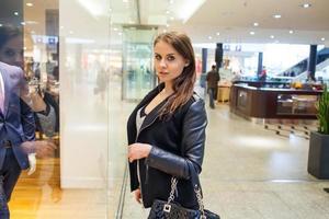 foto av ung glad kvinna med handväska i bakgrunden