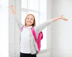student tjej med händerna upp i skolan foto