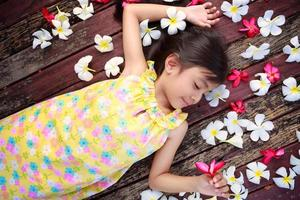 liten asiatisk tjej som ligger på golvet foto