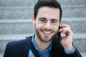 leende ung man ringer via mobiltelefon foto