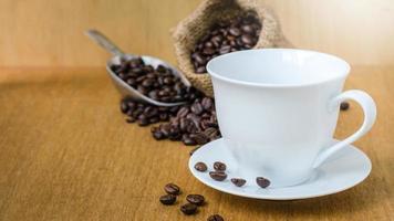 kopp kaffe och kaffebönor på trä foto