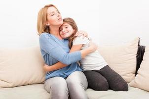 vacker mor och ung dotter kramar foto