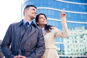 leende par som tittar upp på someting utomhus foto